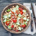 Chickpea salad with cherry tomatoes, cucumbers, basil and onion with citrus dressing, top view, square format Royalty Free Stock Photo