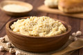 Chickpea spread or hummus with sesame seeds in wooden bowl photographed with natural light selective focus focus one third into Stock Photo