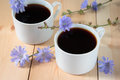 Chicory drink in two white cup cups and flowers Stock Photo