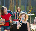 Chidren singer girl singing playing live band in backyard blond kid concert with friends Stock Photography