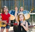 Chidren singer girl singing playing live band in backyard blond kid concert with friends Royalty Free Stock Photo