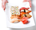 Chief cook holding plate with sushi Royalty Free Stock Image