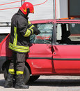 Chief fireman while breaking the glass of a car with a special e Royalty Free Stock Photo