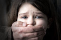 Child abuse scared young girl with an adult man s hand covering her mouth Stock Photo
