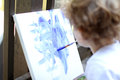 Child art fingerpainting outside on a white canvas with paints Royalty Free Stock Images