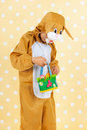 Child as easter hare with eggs dressed basket on yellow dotted background Royalty Free Stock Images