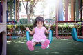 Child asian little girl having fun to play swing in children playground Stock Photo