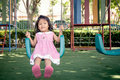 Child asian little girl having fun to play swing in children playground Stock Photography