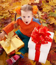 Child  in autumn orange leaves and gift box. Royalty Free Stock Photo