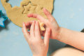 Child baby boy pressing a star cookie cutter into sugar cookie dough. Above view. A heart and a star in the littke hands