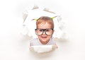 Child baby girl with funny tails with glasses peeping through a hole in white paper an empty poster Stock Photos
