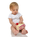 Child baby girl toddler sitting holding piece of candy cake toy