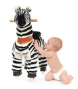 Child baby toddler play with big zebra horse toy Royalty Free Stock Photos