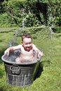 Child bathing outdoors in old bath Stock Photos