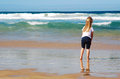 Child on beach back view of a little caucasian girl standing bare feet in the water watching the ocean Stock Image