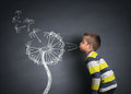 Child blowing dandelion seeds Royalty Free Stock Photo