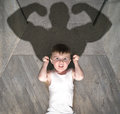 Child bodybuilder a young boy showing his muscles and the shadow of what he could become Stock Images