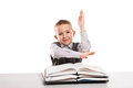 Child with books at desk gesturing hand up for answering school little smiling boy education homework lesson Royalty Free Stock Photo