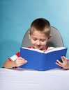 Child boy with a book on blue background holding an open Royalty Free Stock Photography