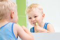 Child boy brushing teeth in bathroom kid Stock Images