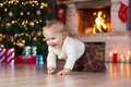 Child boy crawling near Christmas tree in front of Royalty Free Stock Photo