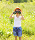 Child boy looks in binoculars outdoors in summer Royalty Free Stock Photo