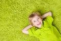 Child Boy lying on green carpet background. Smiling Kid Royalty Free Stock Photo