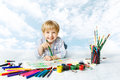 Child boy painting with color brush creative drawing using a lot of tools happy kid artist over blue sky creativity and Stock Photos