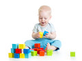Child boy playing toy blocks isolated on white