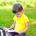 Child boy reading a book on the grass in summer Royalty Free Stock Photo