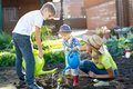 Child boy watering plant with his mother and brothers in garden Royalty Free Stock Photo