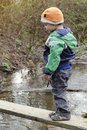 Child on bridge over stream small a simple wooden a in nature Stock Photography