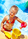 Child with bucket in swimming pool summer outdoor Stock Image