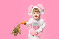 Child in bunny hare costume holding carrots pink background Royalty Free Stock Image