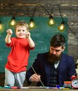 Child cheerful and teacher painting, drawing. Art lesson concept. Teacher with beard, father teaches little son to draw Royalty Free Stock Photo