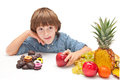 Child choosing food boy between healthy and chocolate sweets Royalty Free Stock Images