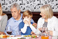 Child cleaning mouth with napkin at family dinner Stock Photos