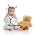 Child with clothes of doctor and teddy bear Royalty Free Stock Images