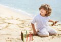 Child with color pencils on sunny beach beautiful boy sandy against sea background Royalty Free Stock Photos