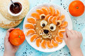 Child cooking and eating funny breakfast lion pancake with tange Royalty Free Stock Photo