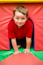 Child crawling through tunnel on play mats Royalty Free Stock Photos