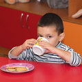 Child with cup boy eats cookies and drinks from a Stock Photos