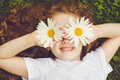 Child with daisy eyes, on green grass in a summer park. Royalty Free Stock Photo