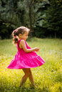 Child dancing in nature girl pink clothes on grass Stock Image