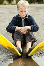 Child daydreaming while wearing diving flippers single sitting on ground next to muddy puddle in gravel yellow and black Stock Images