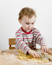 Child at desk making cookies wooden vertical image Stock Image
