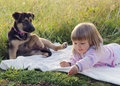 Child with dog in nature girl puppy relaxing on blanket grass at meadow Stock Photos