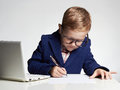 Child doing homework.Young business boy in office.kid in glasses writing pen Royalty Free Stock Photo
