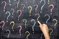 Child drawing colorful question marks on blackboard Royalty Free Stock Photo