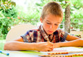 Child drawing outdoors scoolboy sitting at table Stock Images